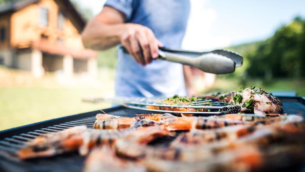 a close up of a person using a BBQ