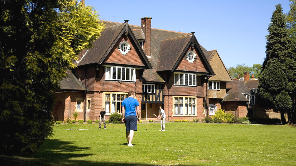 a group of people playing frisbee in a yard