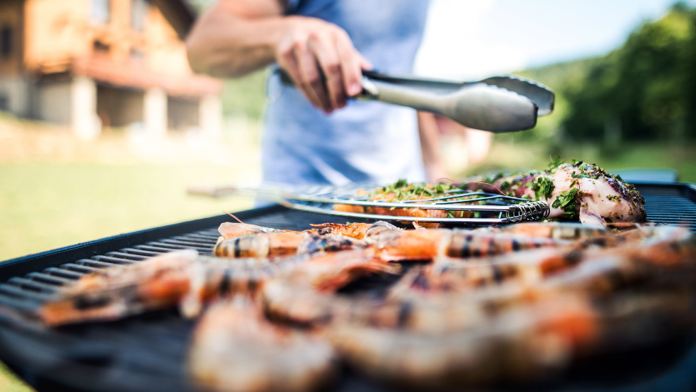 a close up of a person cooking food on a BBQ