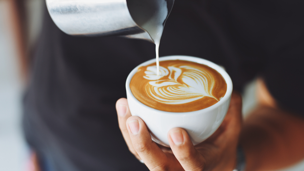 a person pouring milk into a cup of coffee