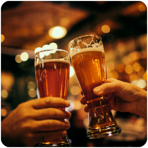 two people handing a glass of beer