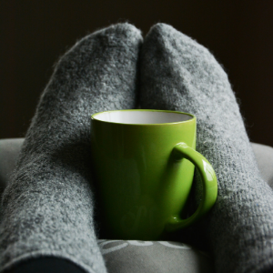 a close up of a coffee cup and some feet in wooly socks