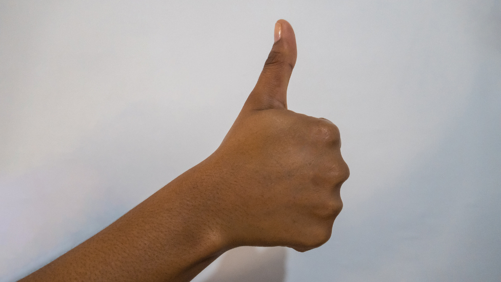 a close up of a hand doing thumbs up