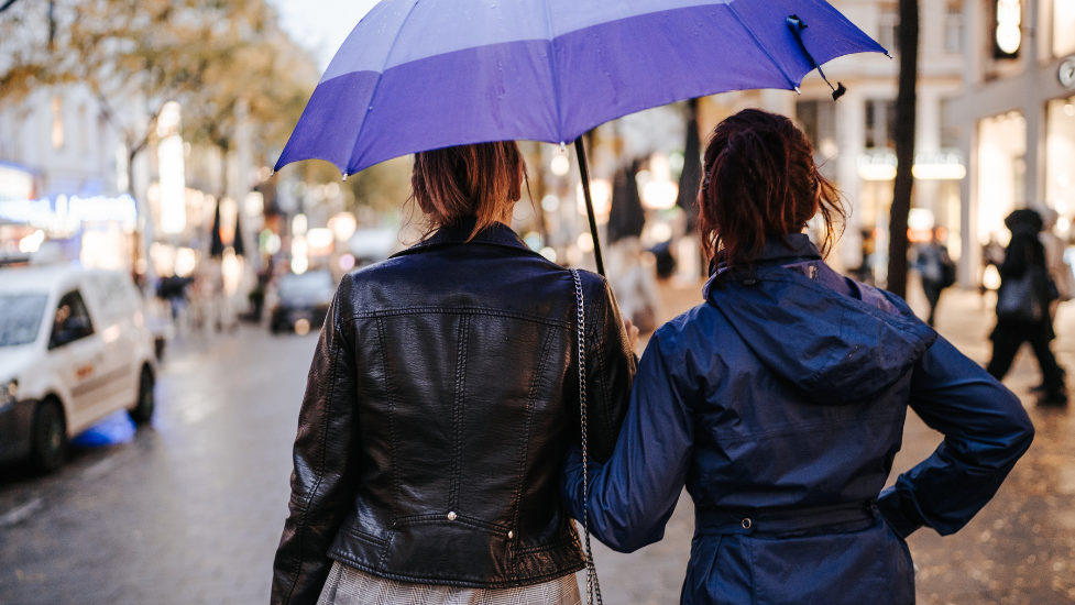 two people walking down a street holding an umbrella