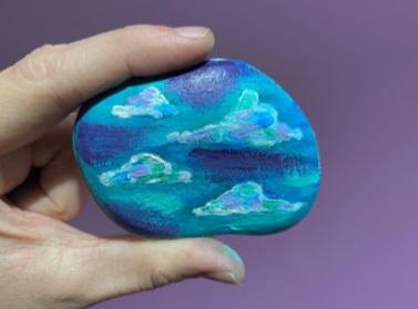 a hand holding a blue painted stone