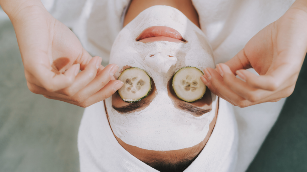 a close up of a person with a face mask on and cucumber over their eyes