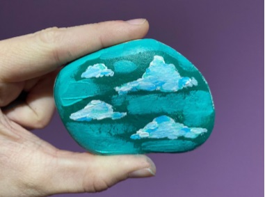 a hand holding a blue stone painted