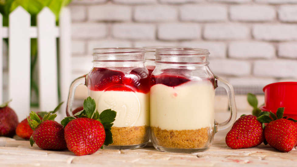 a cake in a jar with strawberries next to them