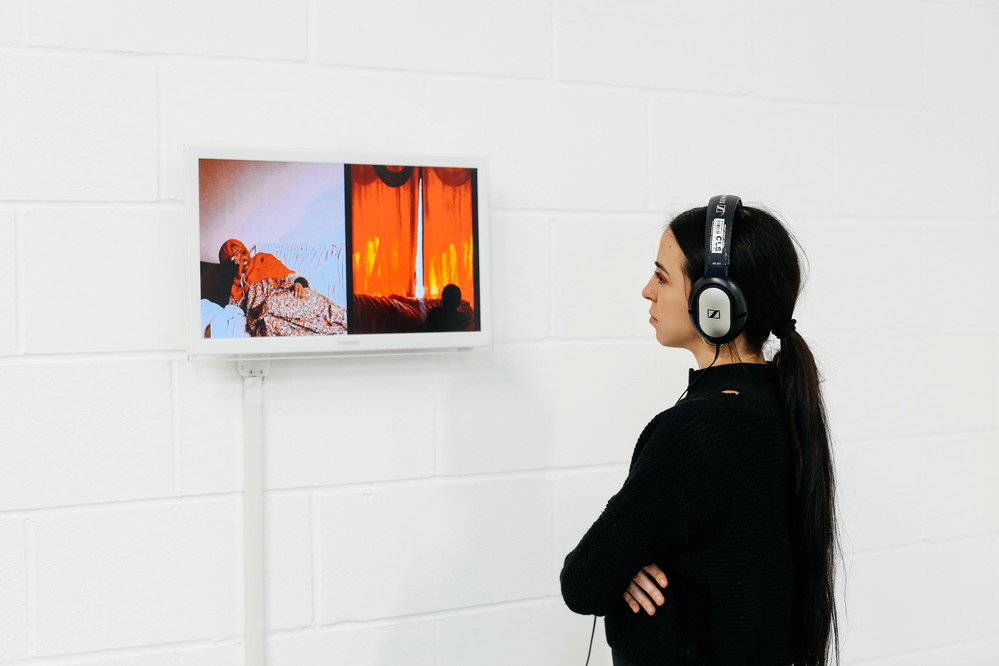 a person standing in front of some art work with headphone