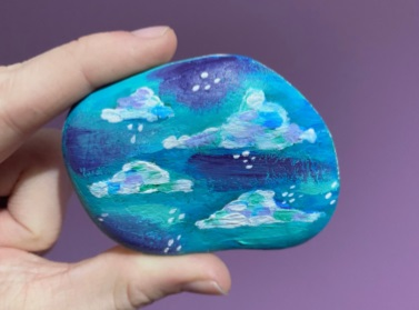 a hand holding a blue painted stone with clouds and raindrops