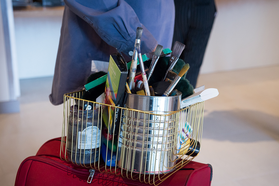 a close up of a basket with art supplies on a suitcase of a student moving in