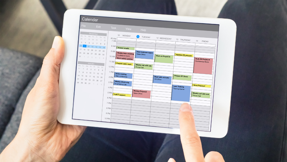 a hand holding an iPad with an online calendar showing