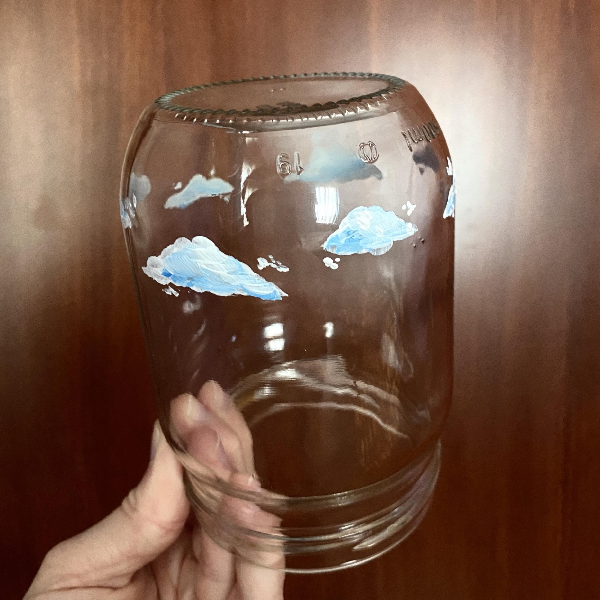 a person holding a glass jar with clouds painted on