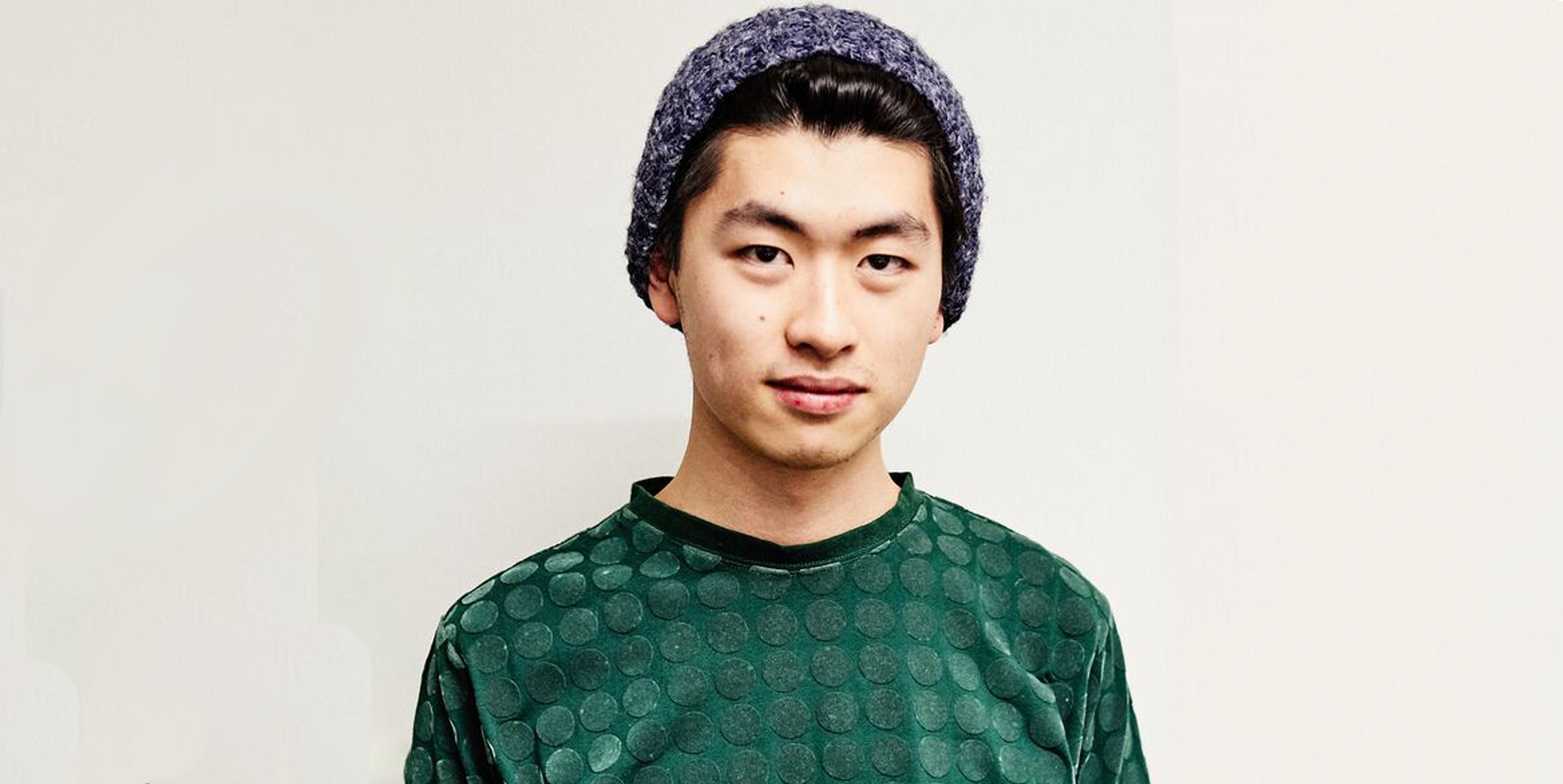 a young man wearing a green shirt