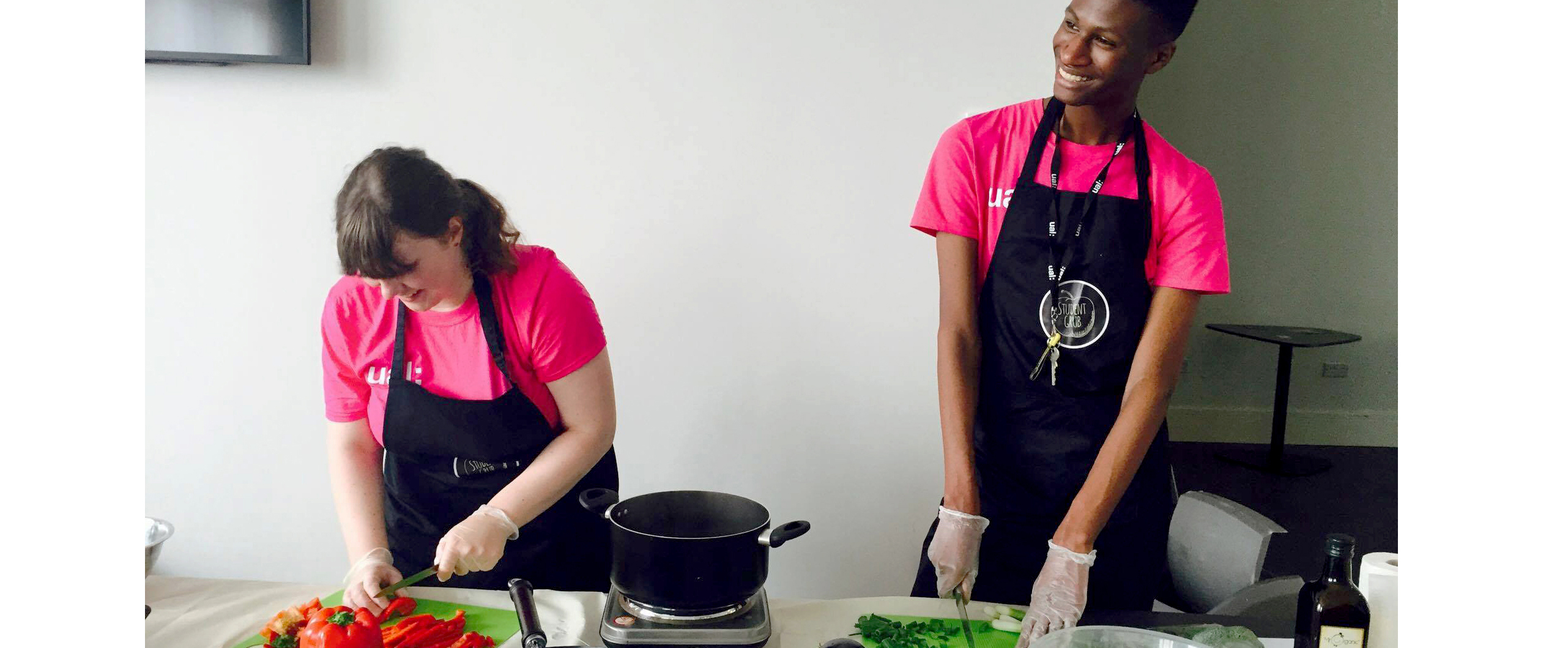 a man and woman preparing food in a kitchen
