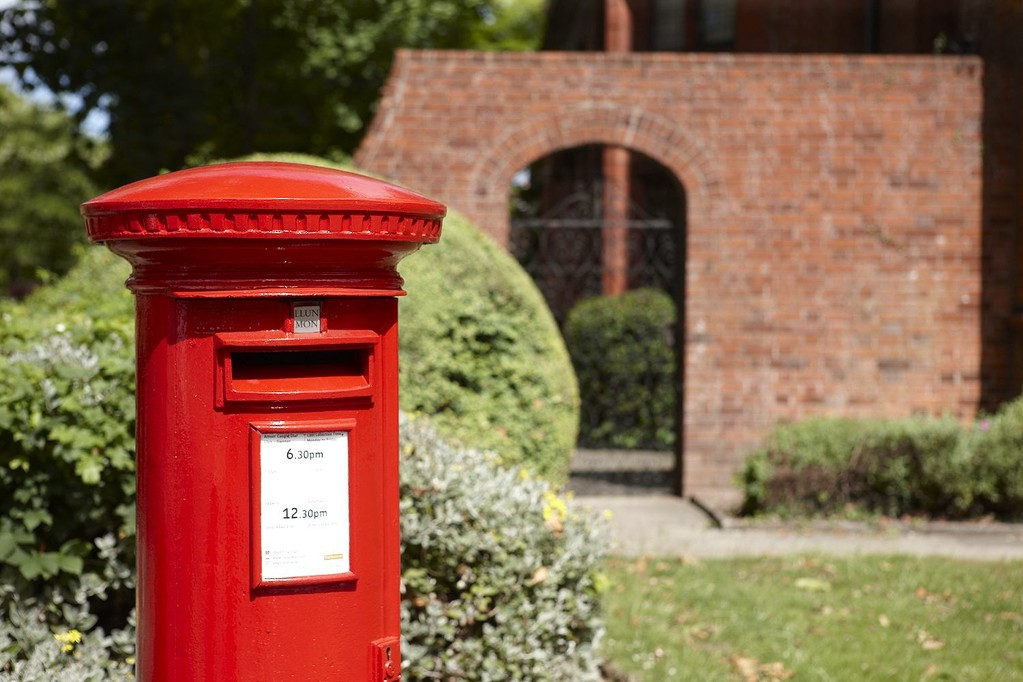 a postbox in front of a brick building