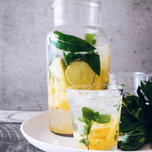 a jug and glass of water with lemon and mint