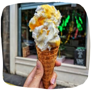 a person holding up ice cream in a cone